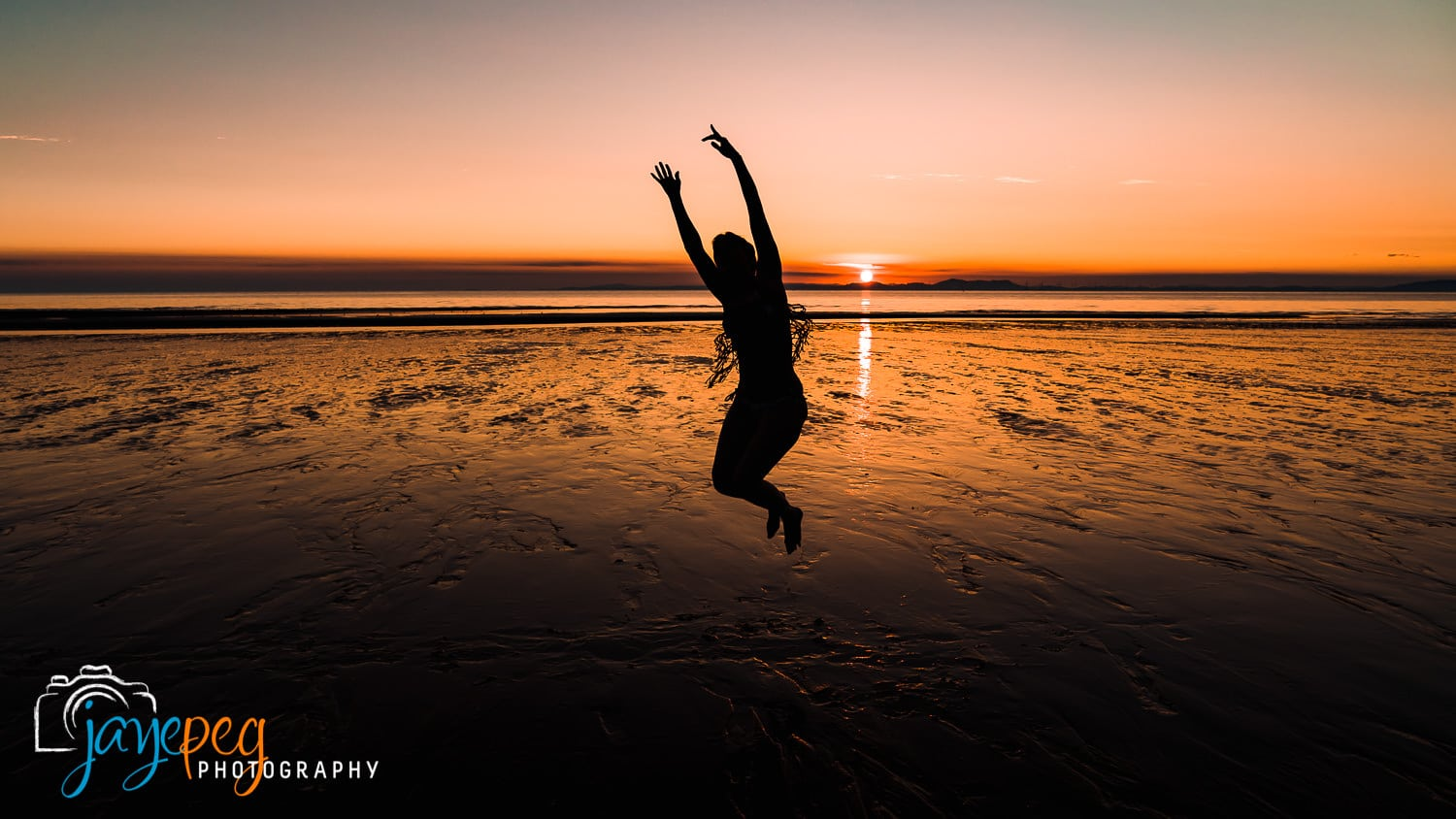 a photograph of a dancer in silhouette jumping on the beach at sunset in cumbria