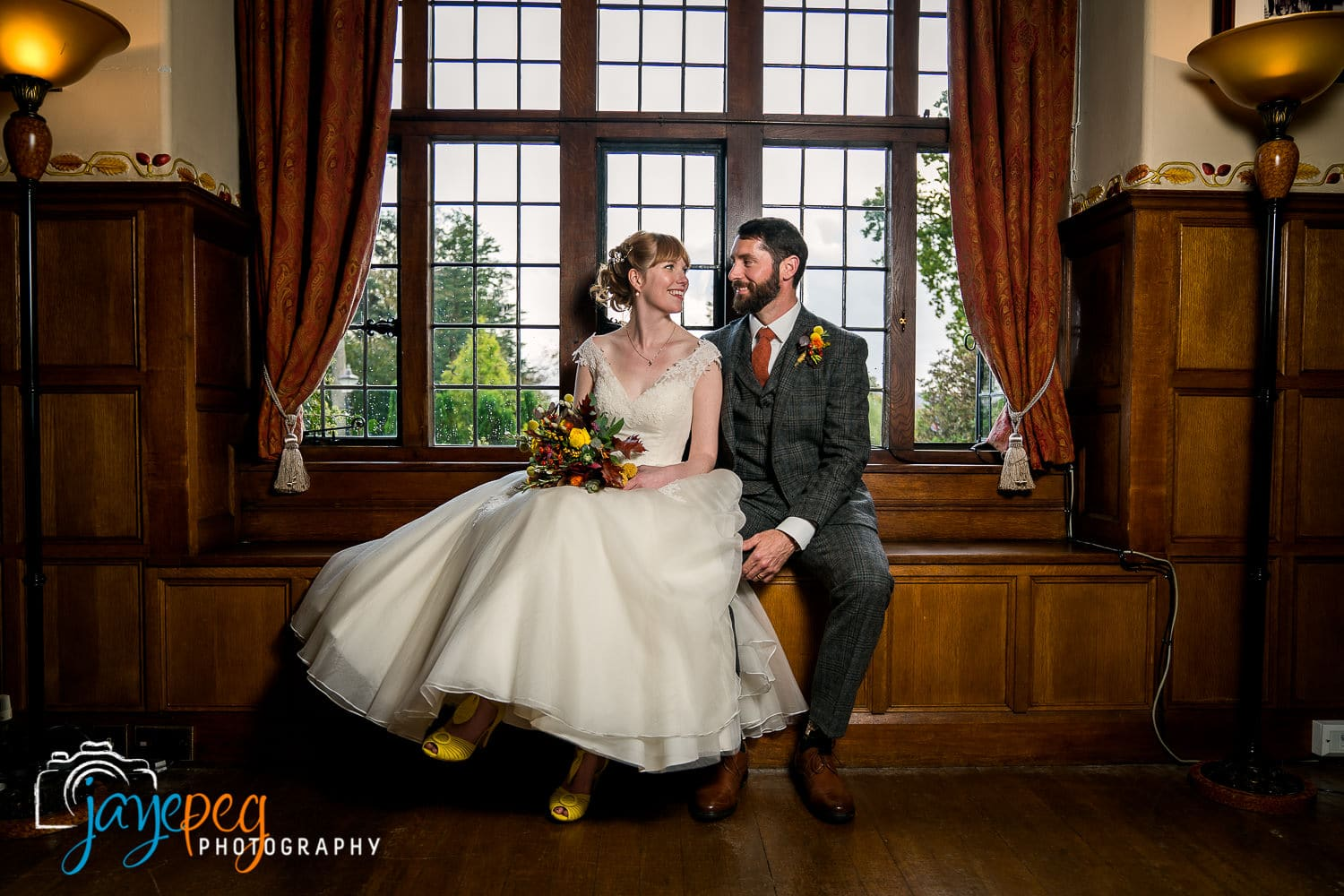 bride and groom sat on the window seat in the music room at broadoaks country house hotel
