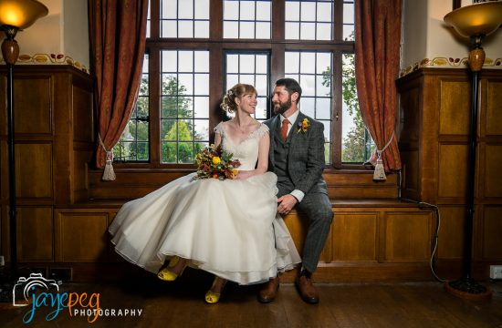 bride and groom sitting in the window seat of the music room at broadoaks country house hotel in trout beck bridge near windermere