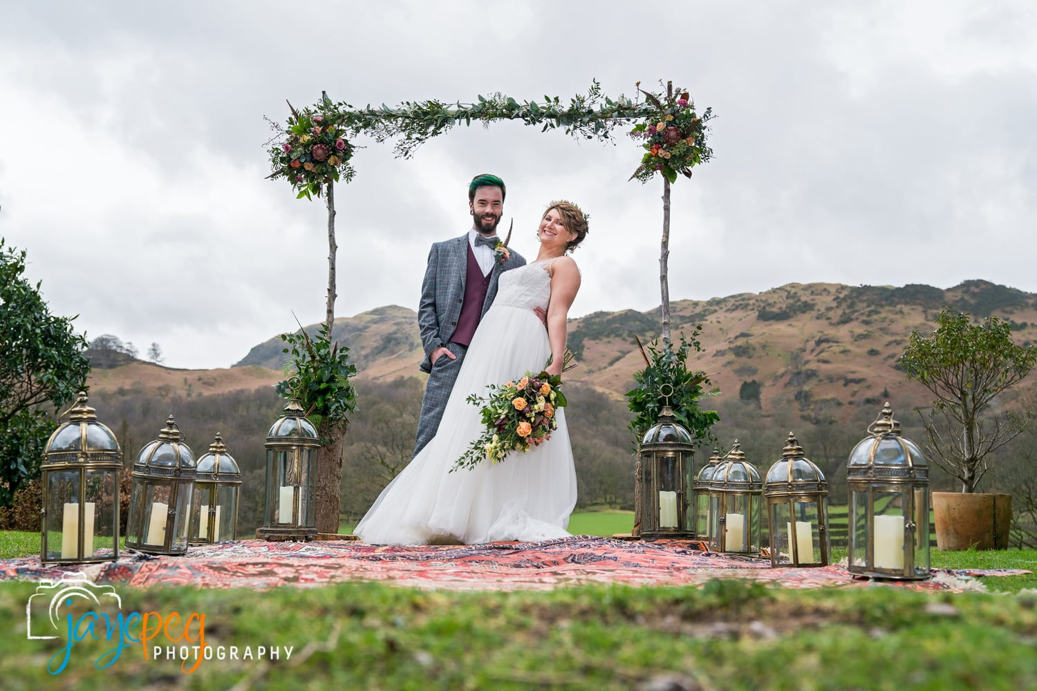 bride and groom under a rustic flower arch over persian rugs and surrounded by lanterns in grasmere at the lancrigg hotel