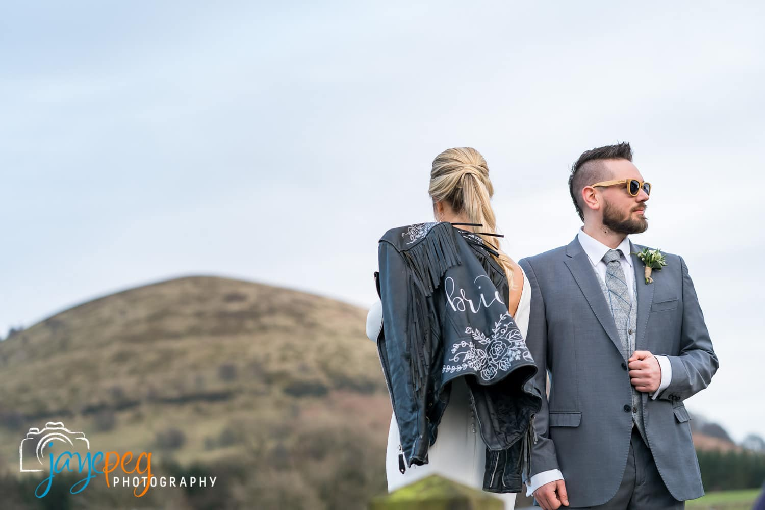 bride with leather jacket and groom with sunglasses framed against a beautiful blue sky