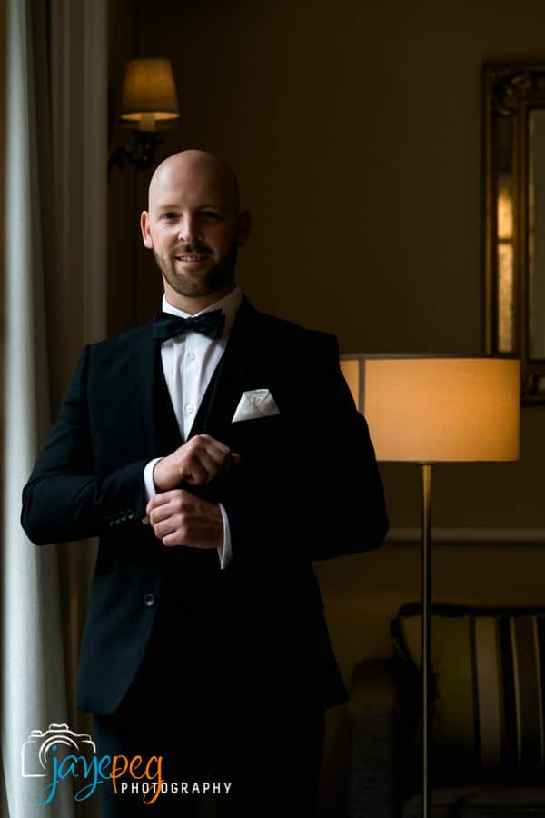 groom portrait lit through an open doorway