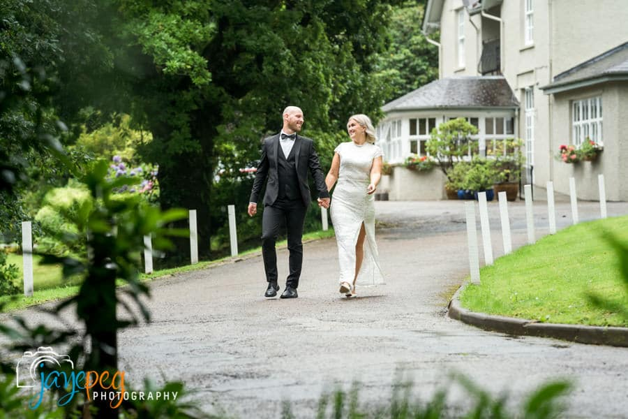 bride and groom walking hand in hand along the driveway at briery wood country house hotel near windermere