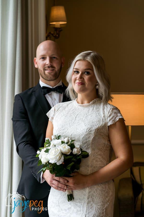 bride and groom portrait lit through an open doorway