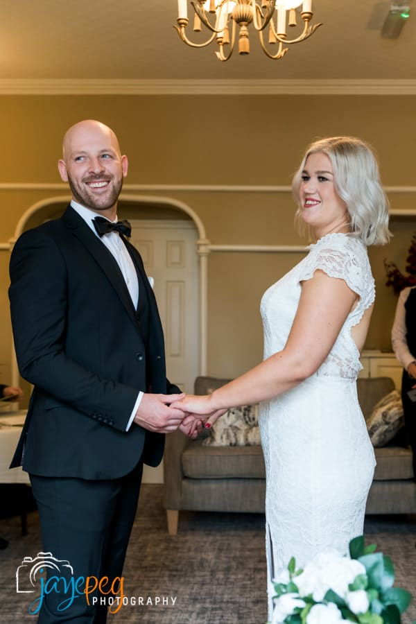 groom and bride holding hands as they take their wedding vows