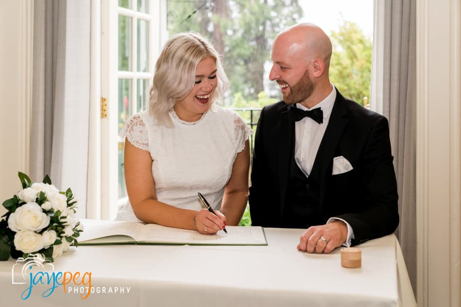 bride and groom signing the register after their micro wedding ceremony