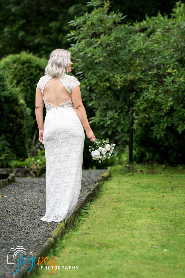 bride standing on a footpath holding her bouquet