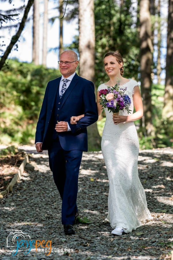 a father walks his bride to her wedding ceremony