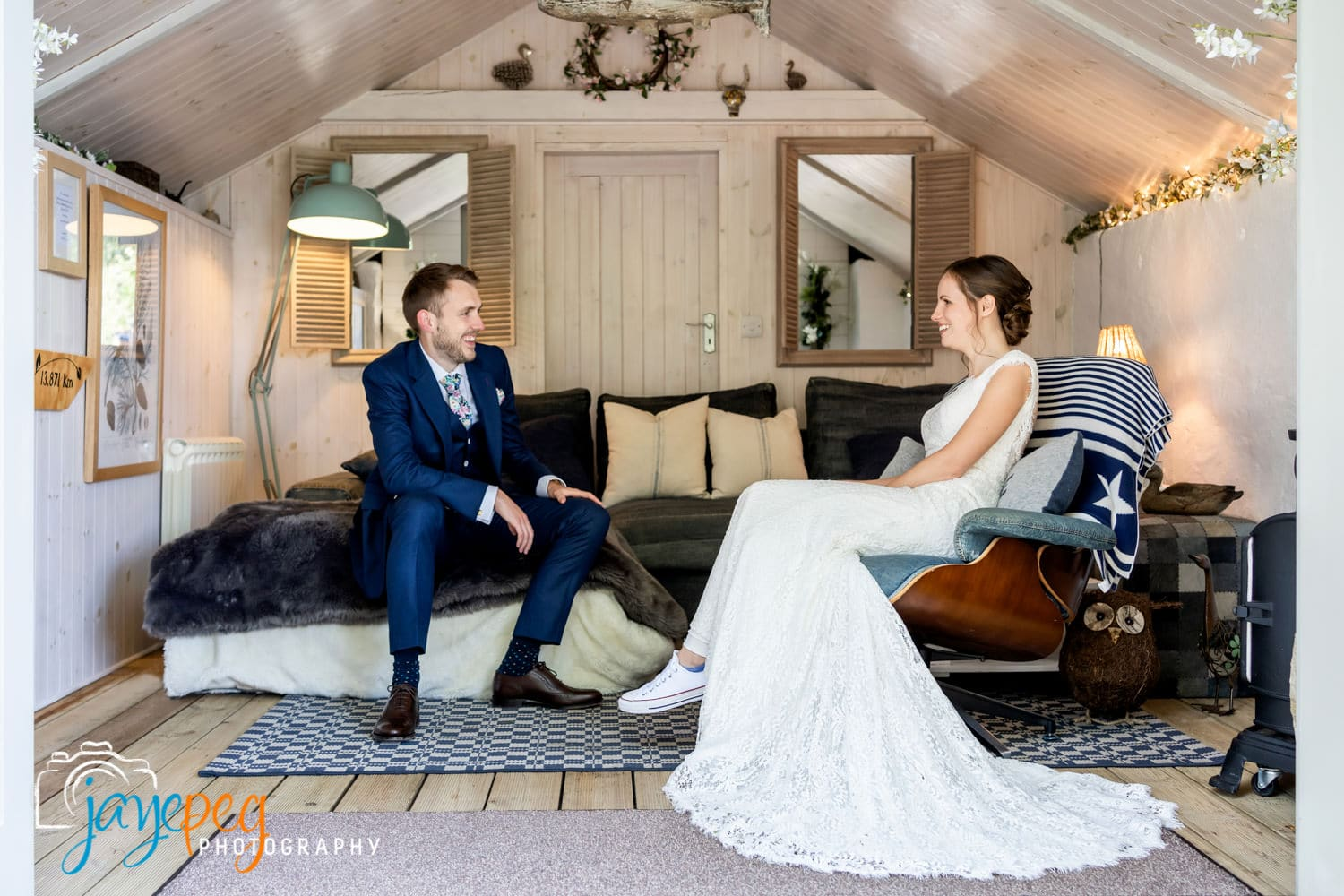 a groom and a bride relaxing in the boathouse at gilpin lake house
