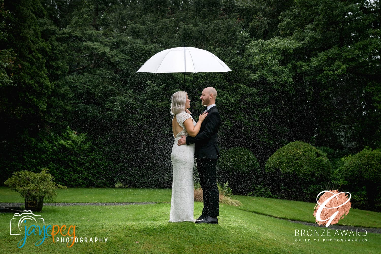 bride and groom under an umbrella in the rain