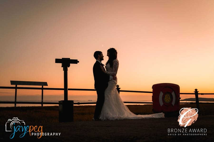 a bride and groom at sunset on grange over sands promenade