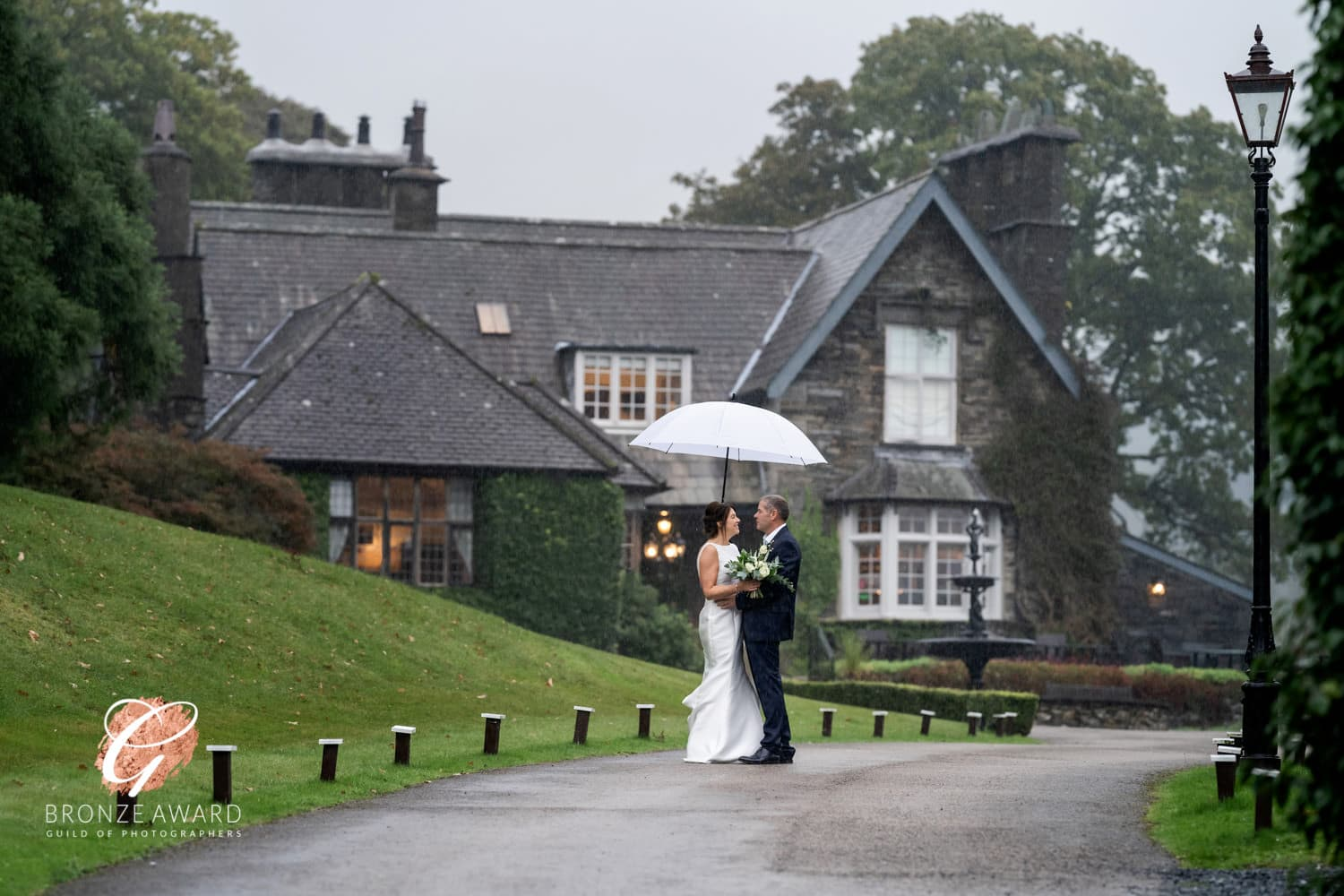 a bride and groom under an umbrella in the rain at broadoaks country house hotel