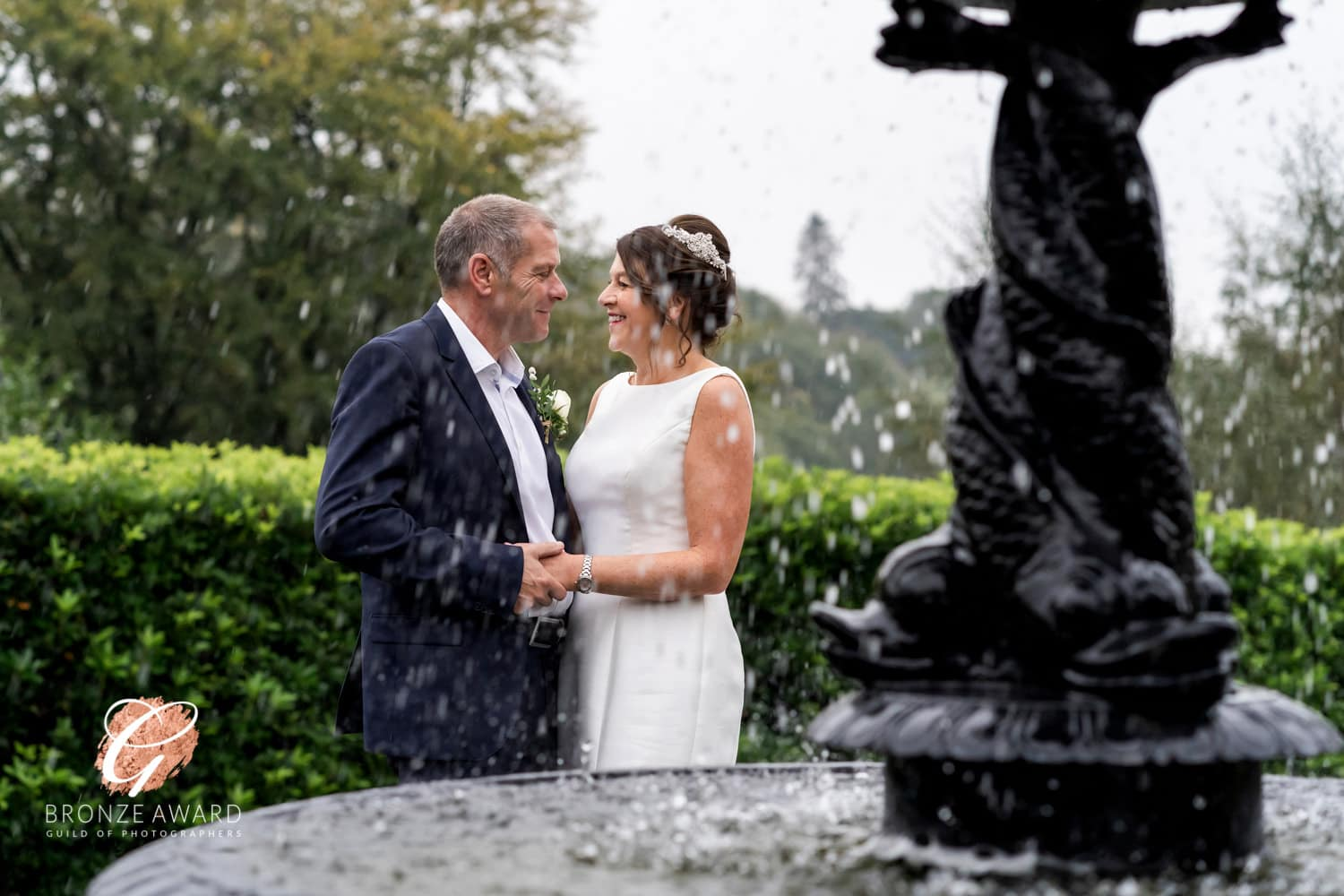 a bride and groom by athe fountain at broadoaks country house hotel