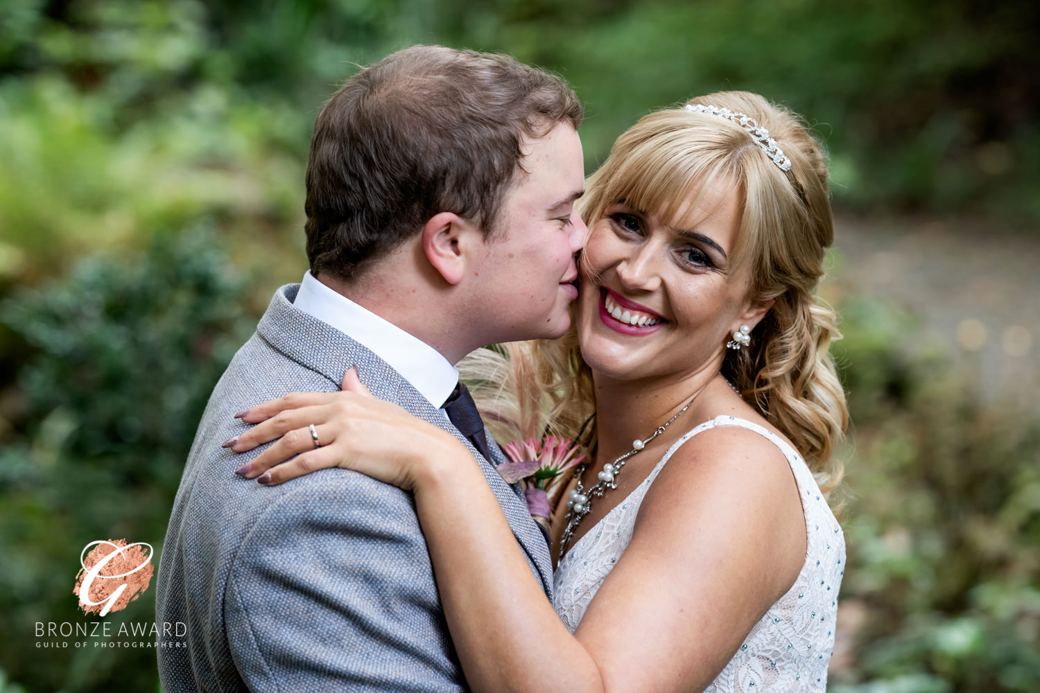 an award winning photograph of a groom kissing his bride while she smiles