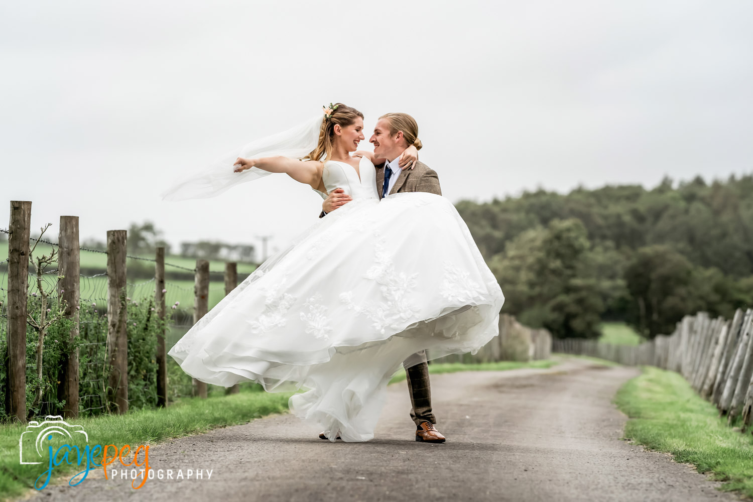 groom carries bride along a driveway